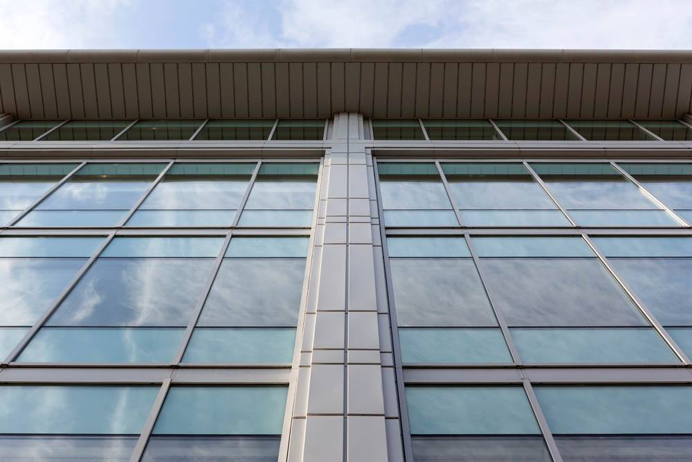 curtain walling windows on side of large office building looking up from ground
