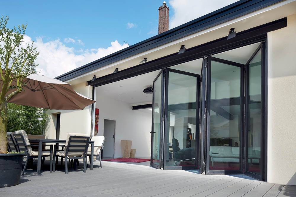 back garden aluminium bi fold doors opening onto grey decking
