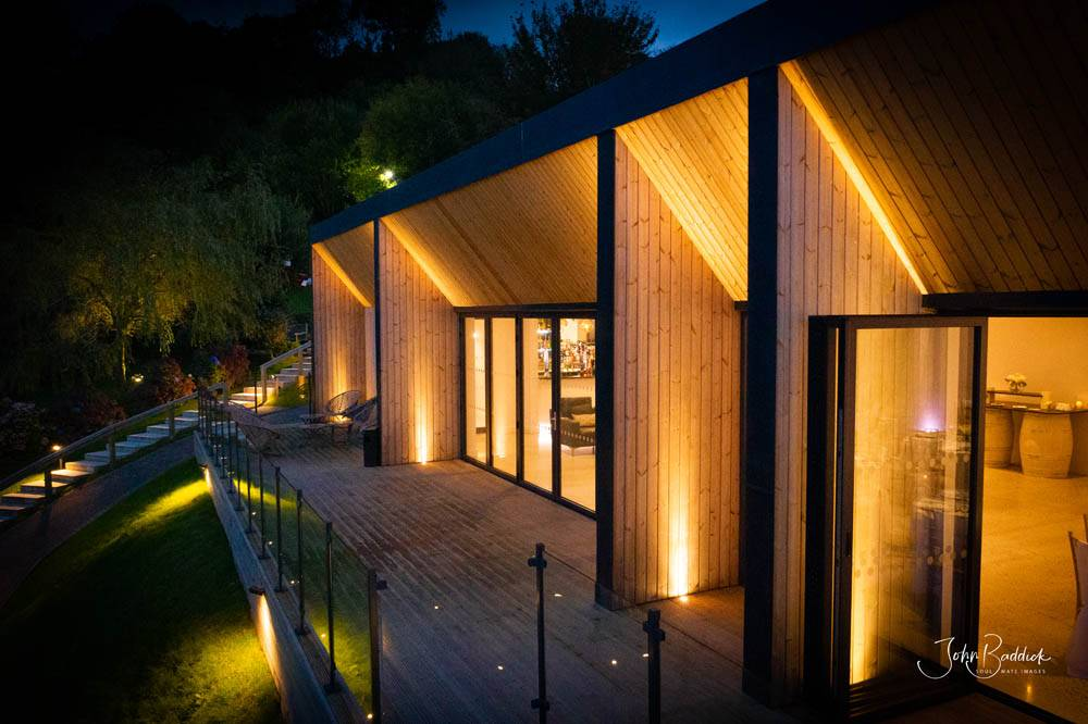 Alumitech sandy cove project lit up at night bi fold doors