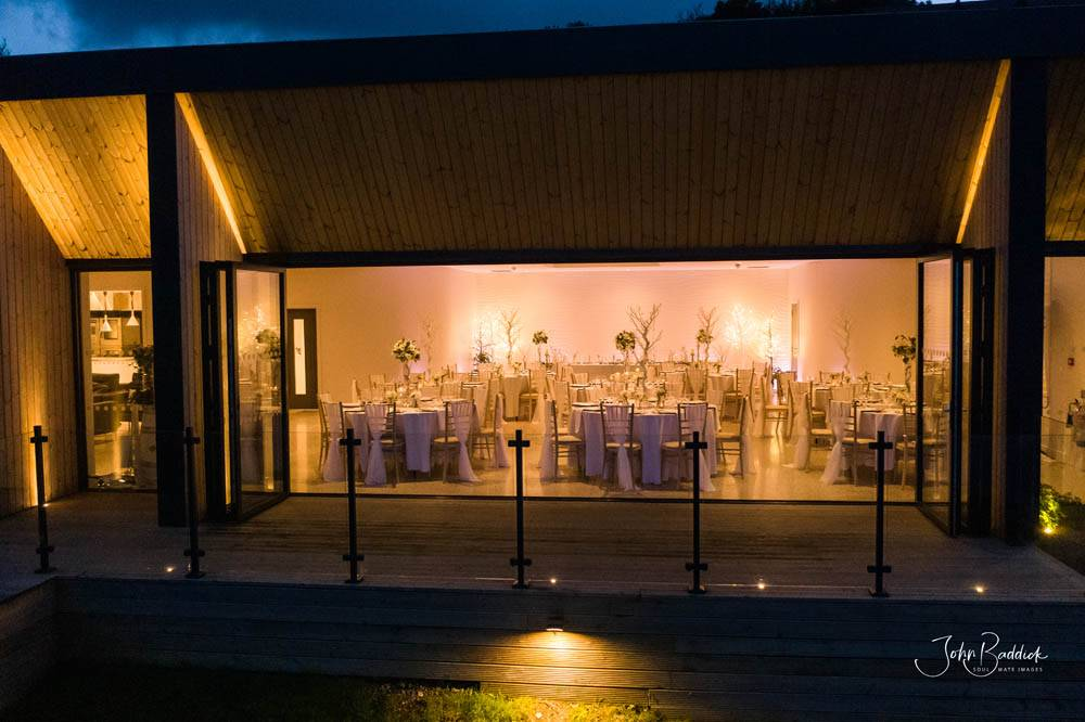 Alumitech sandy cove project lit up at night bi fold doors open