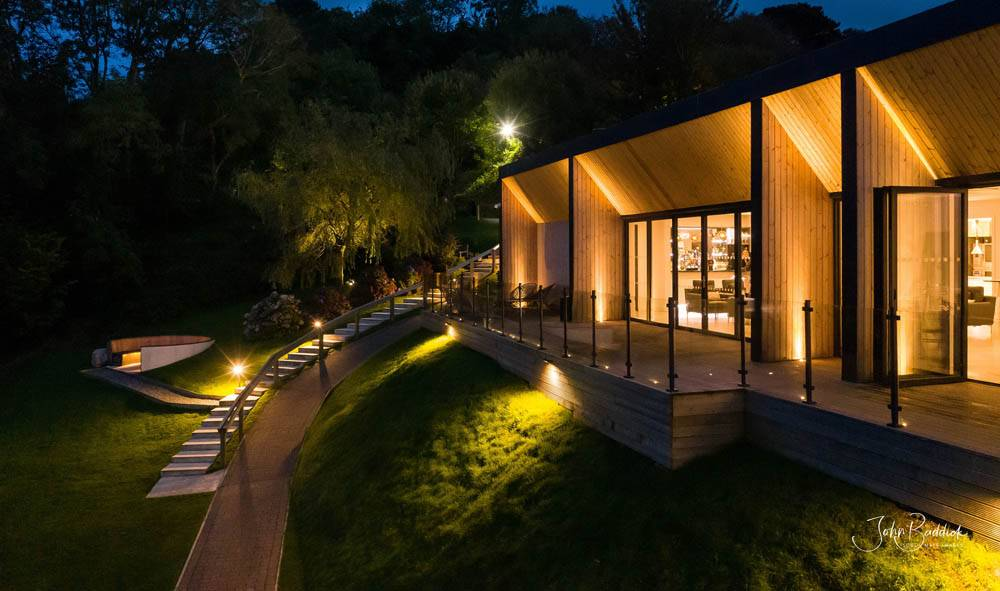 Alumitech sandy cove project lit up at night bi fold doors and walkway