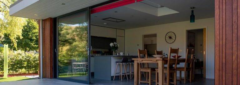 large aluminium framed sliding doors leading from kitchen to patio area of modern home